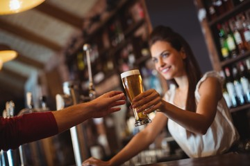 Female bar tender giving glass of beer to customer
