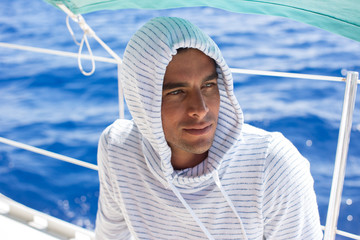 Man on boat, shaded by canopy, Tahiti