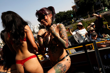 """Tourists take pictures of exotic models and porn actresses standing on the top of a bus waving to people to promote the """"Expo Sex and Eroticism"""" adult exhibition in Mexico City"""