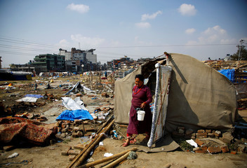 A woman carrying her belongings walks out from the makeshift shelter before it was demolished at the displacement camp for earthquake victims at Chuchepati in Kathmandu