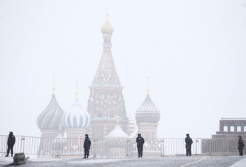 Police block access to Red Square during snowfall, with St. Basil's cathedral seen in background, in central Moscow