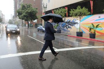 A man walks through heavy rain in Los Angeles