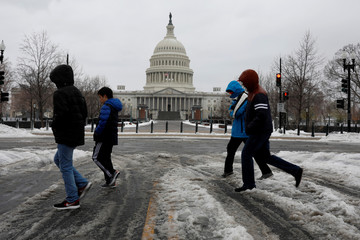 People walk through the snow outside the Capitol Building in Washington, D.C.