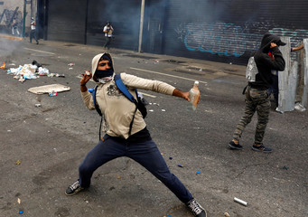A demonstrator throws stones during a rally against Venezuela's President Nicolas Maduro's government in Caracas