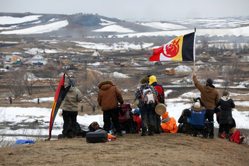 Protesters watch law enforcement officers sweep through the main opposition camp against the Dakota Access oil pipeline near Cannon Ball