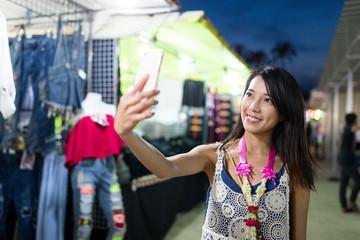 Woman taking selfie by mobile phone in street market