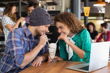 Happy couple looking at each other while having milkshake