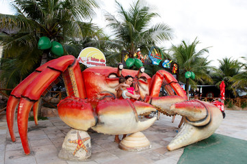 A woman holds a baby as they pose for photos with a sculpture of a large crab in front of a restaurant at Futuro beach in Fortaleza