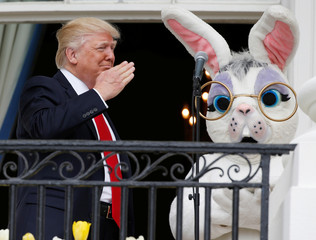 U.S. President Trump salutes a member of the military who had sung the national anthem as he stands with Easter Bunny character at White House Easter Egg Roll in Washington