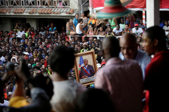 A man holds an image of Haitian President Jovenel Moise as Moise gives a speech during the parade of the Carnival in Jacmel, Haiti