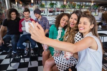 Cheerful female friends taking selfie in restaurant