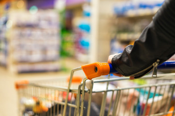 Abstract photo of woman carrying a cart or trolley in the supermarket. Blurred background