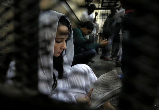 Aya Hijazi, founder of Belady, an NGO that promotes a better life for street children, sits reading a book inside a holding cell as she faces trial on charges of human trafficking at a courthouse in Cairo