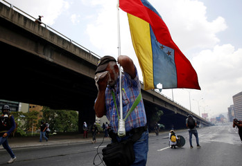 """A demonstrator carries Venezuela's flag while clashing with riot police during the so-called """"mother of all marches"""" against Venezuela's President Maduro in Caracas"""
