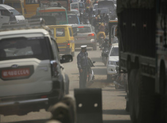 A traffic police wearing a mask stands in between vehicles on a dusty road in Kathmandu