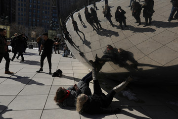 People pose for photos at the Cloud Gate public sculpture on a sunny day