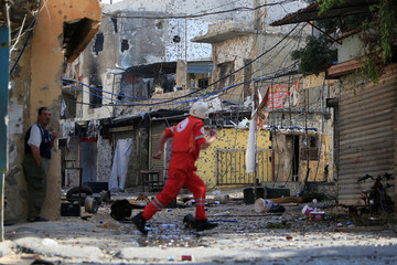 A medic runs as he crosses a street at the Ain el-Hilweh refugee camp near Sidon