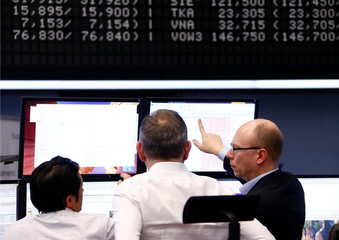 Traders look at their screens at the stock exchange in Frankfurt