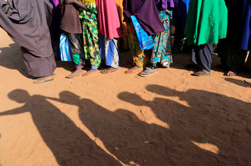 Somali internally displaced children queue before getting into a classroom at a school beside an IDP camp in Dollow