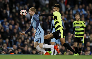 Manchester City's Kevin De Bruyne in action with Huddersfield Town's Philip Billing