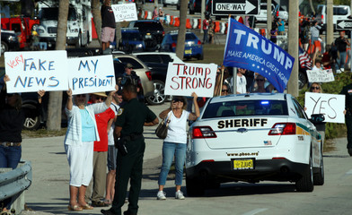 Signs are held aloft as the motorcade of U.S. President Donald Trump drives through West Palm Bech, Florida