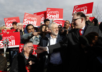 Jeremy Corbyn, the leader of Britain's opposition Labour Party, speaks to supporters after Labour's candidate Gareth Snell (R) won the by-election in Stoke