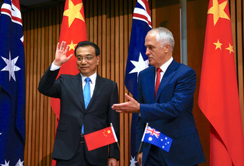 Australia's Prime Minister Malcolm Turnbull gestures to Chinese Premier Li Keqiang at the end of an official signing ceremony at Parliament House in Canberra