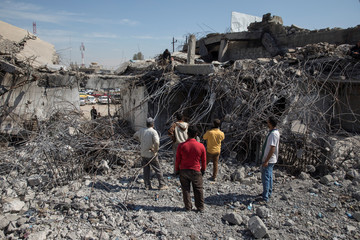 People collect steel from a destroyed building in Mosul