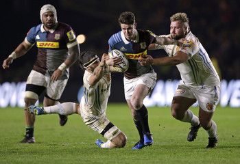 Tim Swiel of Harlequins is tackled by Don Armand (L) and Tomas Francis of Exeter Chiefs