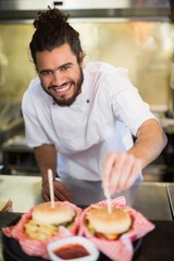 Male chef preparing burger in commercial kitchen