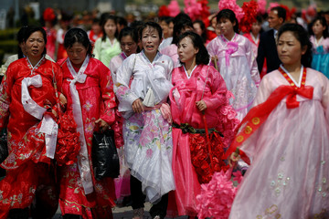 Women in traditional clothes carry plastic flowers after a military parade marking the 105th birth anniversary of North Korea's founding father, Kim Il Sung in Pyongyang