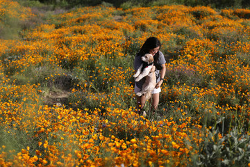 A woman walks through a massive spring wildflower bloom caused by a wet winter in Lake Elsinore