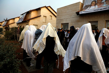 Pro-settlement activists pray outside houses that about to be evacuated in the settlement of Ofra in the occupied West Bank, during an operation by Israeli forces to evict the houses
