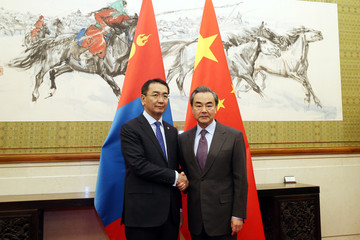 Mongolian Foreign Minister Tsend Munkh-Orgil shakes hands with Chinese Foreign Minister Wang Yi ahead of a meeting at the Diaoyutai State Guesthouse in Beijing