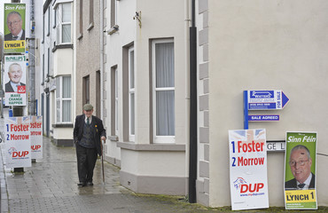 A man walks past political campaign posters on polling day for the Northern Ireland Assembly elections in Brookeborough