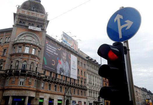 "Traffic lights switch to red in front of a Hungarian pro-Olympics billboard with two-times sabre fencing Olympic champion Szilagyi advertising the Games, billboard saying ""Give it all for the Budapest Olympics"" in central Budapest"