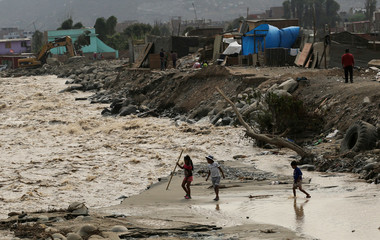 Children play next to Rimac river, after rivers breached their banks due to torrential rains, causing flooding and widespread destruction in Huachipa, Lima
