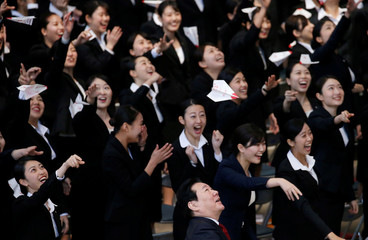 JAL Co's President Ueki and newly-hired employees of JAL group fly paper planes during an initiation ceremony at a hangar of Haneda airport in Tokyo