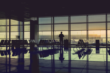 Silhouette passenger at the airport terminal during sunrise. Travel Concept. Vintage colors