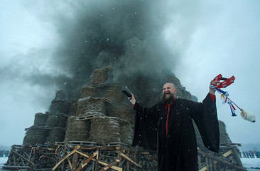 Artist Vinogradov acts in the performance of the burning of Maslenitsa tower, devoted to Pancake Week, a pagan holiday marking the end of winter, in the village of Nikola-Lenivets.