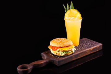 Closeup image of cheeseburger at wooden board and plastic glass of juice at black background.