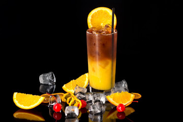 Closeup glass of fresh orange juice mixed with coffee isolated at black background.