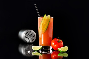 Fresh glass of bloody mary cocktail decorated with lime and cucumber isolated at black background.