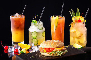Group of fresh summer cocktails and burger at wooden board isolated at black background.