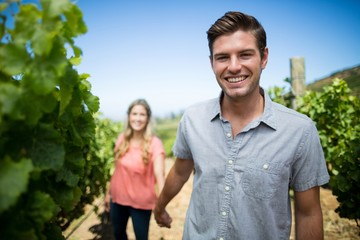 Happy young man holding woman hand at vineyard
