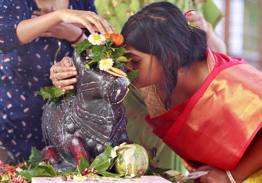 A Hindu woman whispers her wishes in the ear of Nandi (mount of Lord Shiva) inside a temple during the Maha Shivratri festival in Agartala
