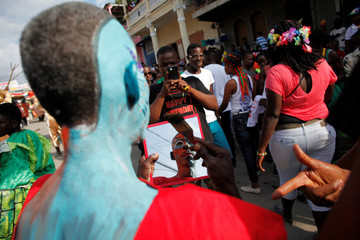 A reveller is reflected in a mirror as he poses for a picture during the Carnival parade in Jacmel, Haiti