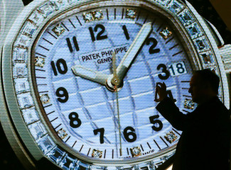 Visitor takes pictures in front of a display of Swiss watch manufacturer Patek Philippe at the Baselworld Watch and Jewellery Show in Basel
