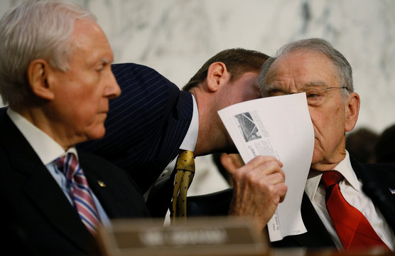 An aide whispers to U.S. Senate Judiciary Committee Chairman Grassley as Senator Hatch looks on during questioning of U.S. Supreme Court nominee judge Gorsuch at his confirmation hearing in Washington
