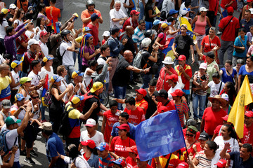 Supporters (in red) of Venezuela's President Maduro and opposition supporters argue in Caracas